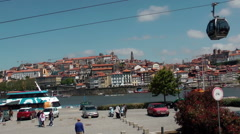 PORTO - MAY 17th,2016 - Cable cars in old port city with river behind Stock Footage