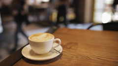 A cup of cappuccino at the entrance to cafe background - stock footage