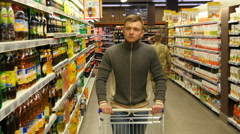 Man with shopping cart walking in the hypermarket Stock Footage