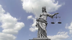 Statue of Lady Justice holding scales and sword in front of a blue cloudy sky. Stock Footage