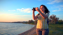 Curly girl in tights takes on the camera of a sunset at the beach. Slow motion Stock Footage