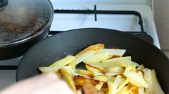 Two pans on the stove first female hand with a wooden spatula prevents crispy Stock Footage