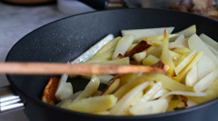 Wooden shovel stirs crisp potato in a frying pan Stock Footage