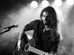 Singing and playing acoustic guitar on stage - stock photo