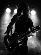Silhouette acoustic guitar player on stage - stock photo