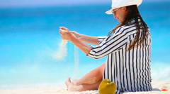 Young beautiful woman on white beach with coconut Stock Footage