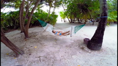 Adorable little girl relaxing in hammock on beach - stock footage