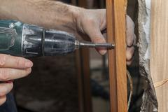 Woodworker screwed the jamb in doorway using a cordless drill electric screwd - stock photo