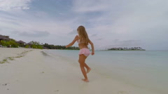 Happy little girl have fun on a beach during summer vacation - stock footage