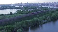 Train passes through the forest against the backdrop of the city, top view Stock Footage