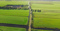 A white van drives towards a drone while it flies backwards on a small road Stock Footage