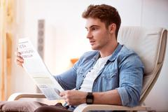 Handsome pleasant man reading newspaper Stock Photos