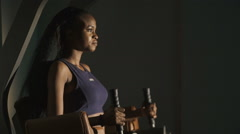 Sexy african american woman with long hair  working out  at the gym simulator Stock Footage