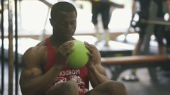 Muscular sweaty african american man   making exercises with ball in the gym - stock footage