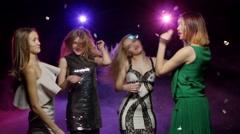 Girls dancing under flying glitter confetti. Dynamic change of focus - stock footage