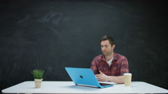 4K Man working on laptop & looking for inspiration on chalkboard background Stock Footage