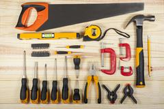 Flat lay display of a workman's toolkit on a wodden background - stock photo