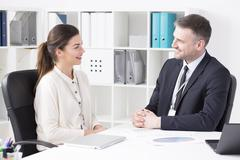 Two office wokers discussing, sitting beside desk in light office - stock photo