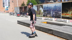 Following a man on rollerskates in a park for leisure activities Stock Footage