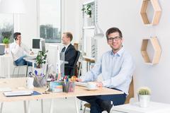 Happy designer sitting beside desk in modern studio, in the background two men d Kuvituskuvat