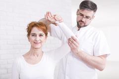 Senior happy woman with shoulder problem exercising with her experienced young p Stock Photos