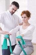 Middle aged physiotherapist training with his older patient stability. Woman sit - stock photo