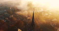 The camera circles around a church covered in fog on an early morning Stock Footage