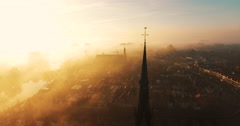 The camera circles around a cross on top of a Christian church covered in fog - stock footage