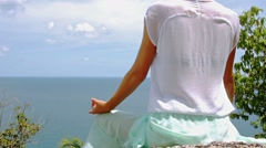 Woman is meditating on a high in front of sea scenery landscape Stock Footage