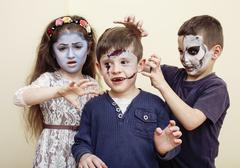 Zombie apocalypse kids concept. Birthday party celebration facepaint on children Kuvituskuvat