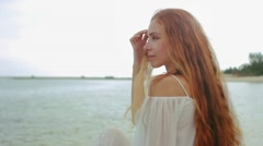 Woman with long red hair at the beach looking to the camera and smiling Stock Footage