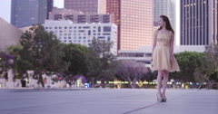 Attractive Asian woman in gold dress in Downtown Los Angeles in evening 4K Stock Footage