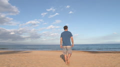 Beach Boy Walks Out To Shore Stock Footage