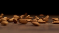 Almonds throwing on a wooden table on a black background. Slow motion. Close up Stock Footage