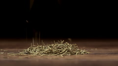 Cumin falling on a wooden table on a black background. Slow motion. Close up - stock footage