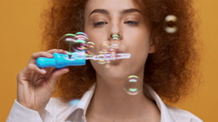 Funny fashion girl blowing soap bubbles on orange background. Close up. Slow - stock footage