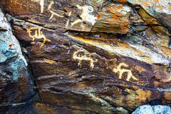 Hunting scenes prehistorical petroglyphs Stock Photos