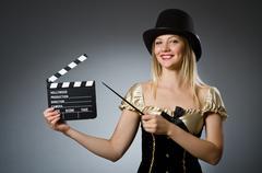 Funny woman in dark studio - stock photo