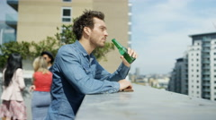 4K Portrait smiling man drinking beer & looking at view at rooftop party Stock Footage
