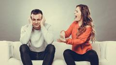 Angry fury woman screaming man closes his ears. - stock photo