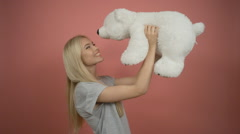 Attractive positive blonde hugging white teddy bear on pink background Stock Footage