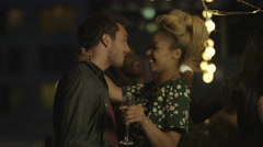4K Happy mixed ethnicity couple drinking & dancing with friends at rooftop party Stock Footage
