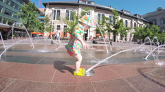 Toddler playing with small fountains on the urban plaza. Stock Footage