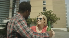4K Happy mixed ethnicity couple chatting & drinking beer at city rooftop party Stock Footage