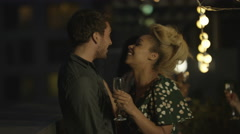 4K Happy mixed ethnicity couple drinking & dancing with friends at rooftop party - stock footage