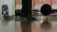 A man hits pins with bowling ball in bowling alley - stock footage