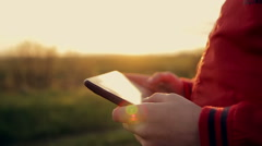 Work and play on the tablet at sunset in the park Stock Footage