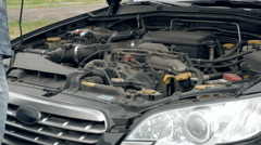 Service man or auto mechanic closes the car hood Stock Footage