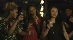 4K Happy mixed ethnicity group of friends drinking & dancing at rooftop party - stock footage