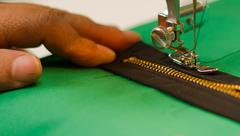 One hand holding a dark zipper, sewing machine making the job on a green fabr Stock Photos